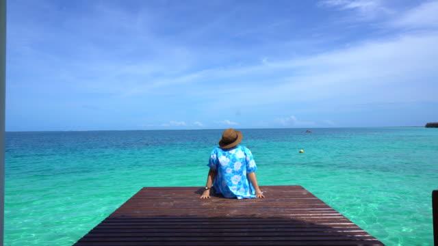 Woman-relax-at-bright-blue-summer-ocean-Enjoying-sea-breeze-on-vacation-4k
