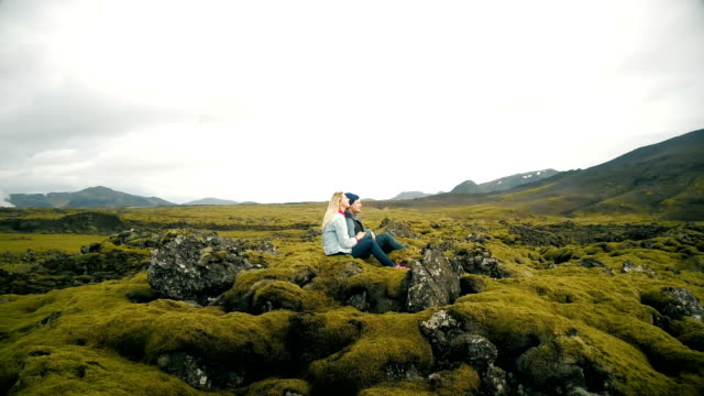 Aerial-view-of-young-beautiful-couple-sitting-and-enjoying-the-landscape-of-lava-field-in-Iceland-Copter-flying-around