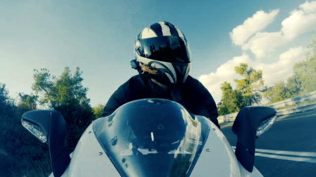 POv-shot-of-a-man-riding-on-a-white-sports-motorcycle-on-a-curved-road