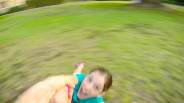 POV-footage-of-father-swinging-his-daughter-outdoors