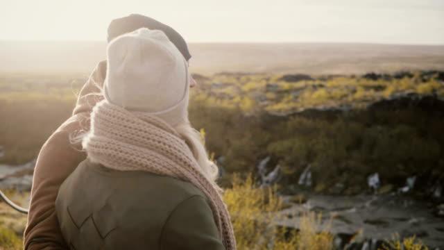 Vista-trasera-del-hombre-joven-y-mujer-de-pie-en-el-valle-soleado-y-disfrutando-de-la-hermosa-vista-en-Islandia