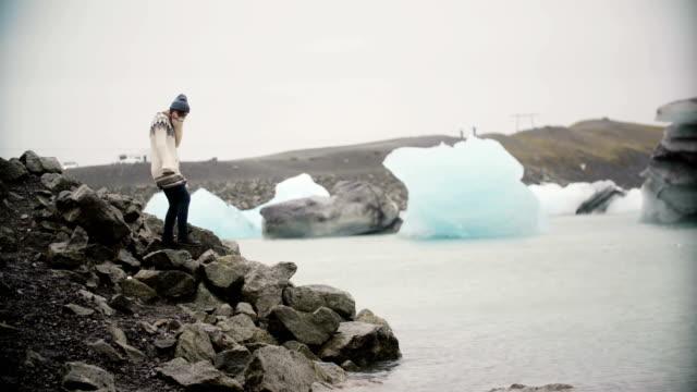 Atractivo-joven-en-lopapeysa-de-pie-en-la-laguna-de-hielo-Turismo-explorando-la-famosa-vista-de-Islandia-solamente