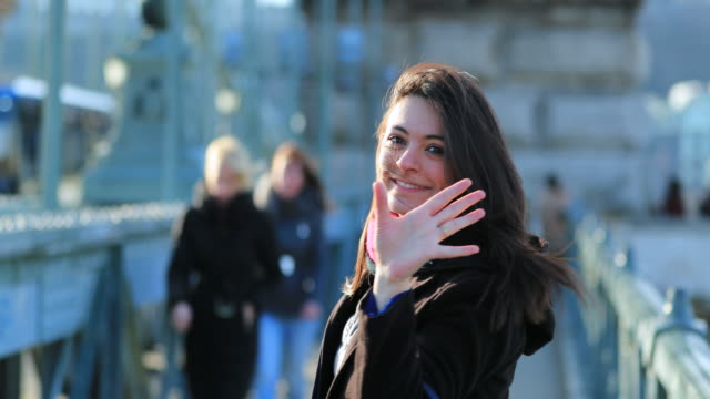 Woman-waving-hello-to-camera-in-4K-welcoming-viewer