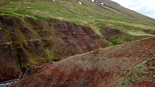 Amazing-drone-point-of-view-of-man-hiking-on-mountain-ridge-over-canyon-in-Iceland