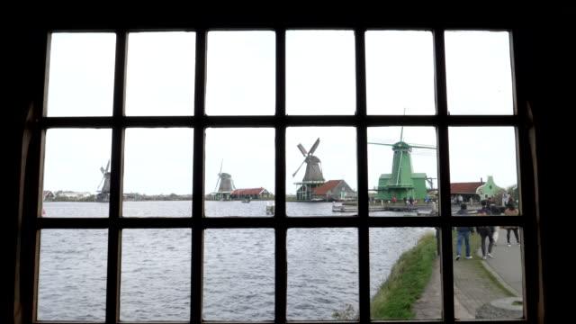 wide-shot-through-a-window-of-windmills-at-zaanse-schans-near-amsterdam