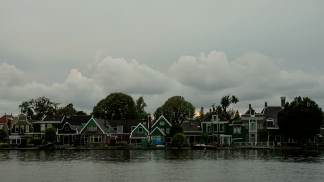 Timelapse-of-clouds-over-houses-on-river-bank-Netherlands