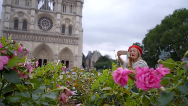 Young-woman-taking-selfie-in-Paris-at-city-Notre-dame-using-mobile-phone