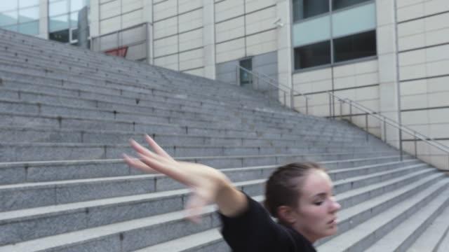 Joven-bailando-en-pasos-de-edificio-de-oficinas