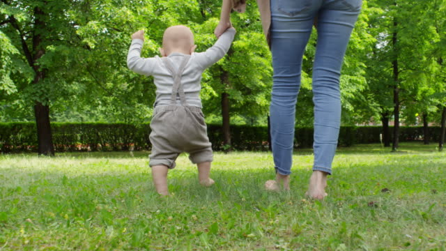 Mother-and-Baby-Boy-Walking-Barefoot-on-Grass