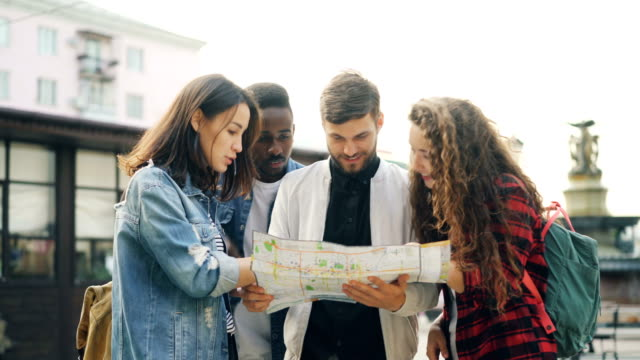 Young-men-and-women-with-backpacks-are-looking-at-map-standing-in-the-street-in-foreign-city-and-talking-discussing-journey-Navigation-youth-and-tourism-concept-