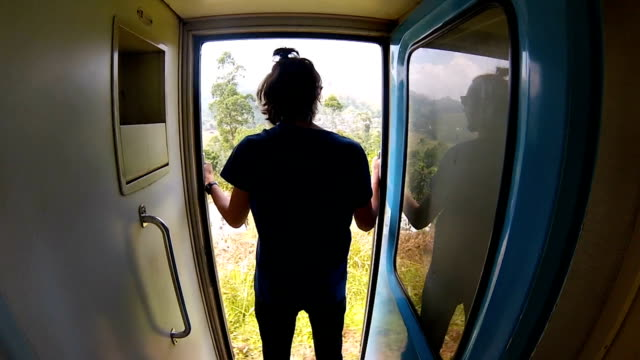 guy-in-the-shirt-rides-the-train-standing-at-the-door