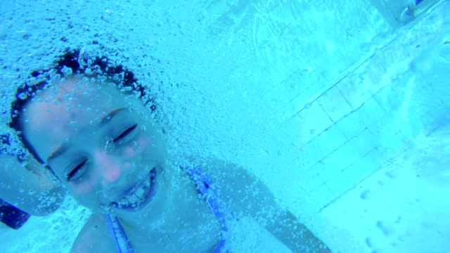Underwater-footage-of-kids-jumping-and-diving-in-a-swimming-pool