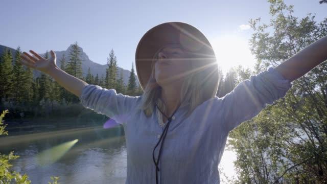 Junge-Frau-Reisen-Kanada-steht-an-den-Fluss-Armen-Vergrösserung