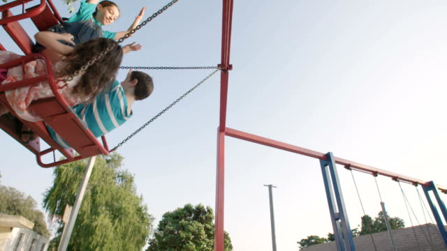 Children-swinging-together-at-a-public-playground