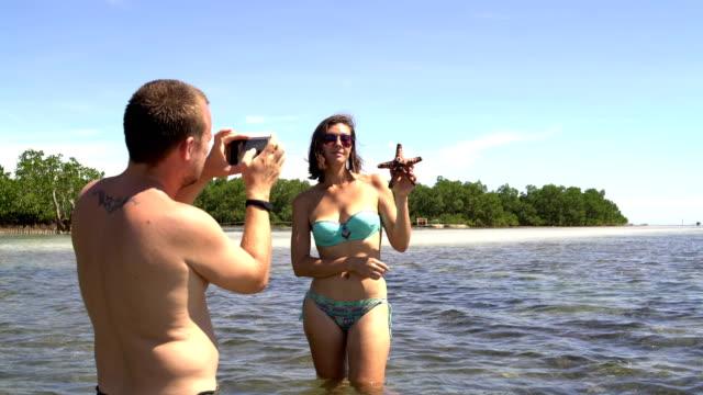 Un-hombre-es-fotografiar-a-una-mujer-en-un-traje-de-baño-de-pie-en-el-mar-con-una-estrella-en-las-manos
