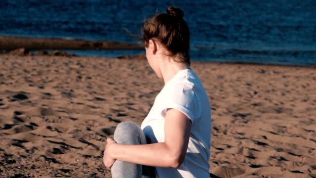 Mujer-de-estiramientos-yoga-en-la-playa-por-el-río-en-la-ciudad-Hermosa-vista-
