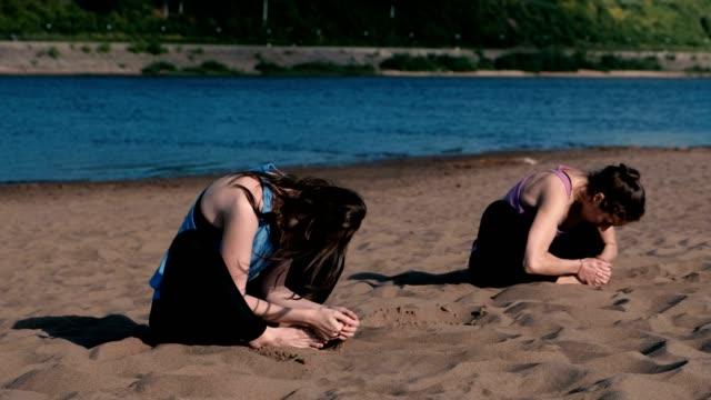 Dos-mujer-haciendo-yoga-en-la-playa-por-el-río-en-la-ciudad-Hermosa-vista-en-la-ciudad-Individuales-de-formación-