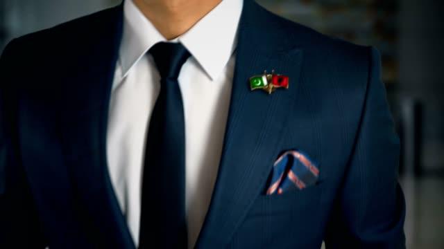 Empresario-caminando-hacia-cámara-con-amigo-país-banderas-Pin-Pakistán---Albania