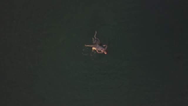 Flying-over-mother-and-son-swimming-in-the-sea