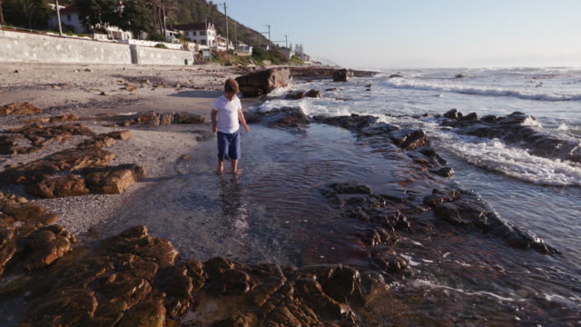 Young-boy-exploring-rock-pool-at-the-beach-in-Cape-Town-South-Africa