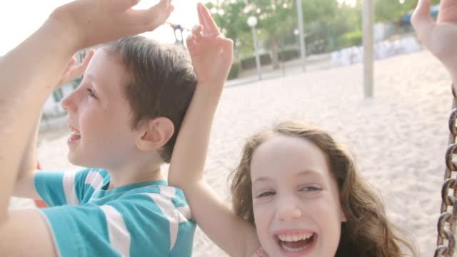 Kinder-schwingen-zusammen-auf-einem-öffentlichen-Spielplatz