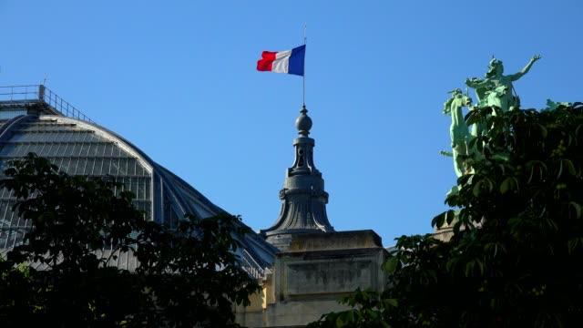 Bandera-francesa-ondeando-en-el-viento-cerca-de-puente-de-Alexandre-III-en-París-Francia