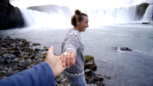 Follow-me-to-the-waterfall-girlfriend-leading-man-to-Godafoss-falls-in-Iceland-People-travel-concept