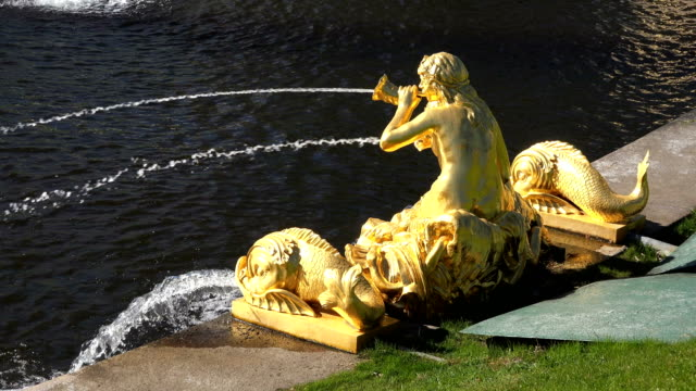 Wasserstrahlen-brechen-aus-einem-Brunnen-mit-vergoldeten-Statuen