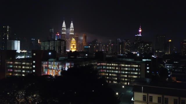 Mover-a-la-izquierda-vista-aérea-de-Kuala-Lumpur-durante-noche-junto-a-la-torre-KLCC-
