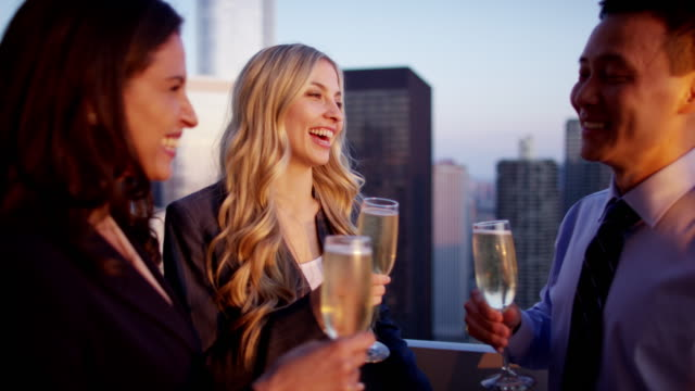 Multi-ethnic-colleagues-with-champagne-on-sunset-rooftop