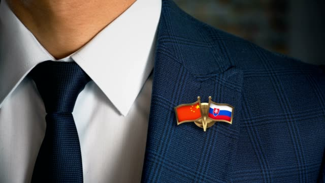 Businessman-Walking-Towards-Camera-With-Friend-Country-Flags-Pin-China---Slovakia