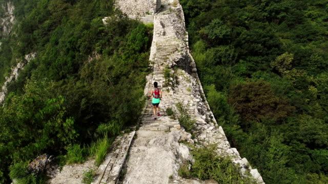 vista-aérea-de-corredor-de-trail-de-mujer-fitness-joven-corriendo-encima-de-gran-muralla