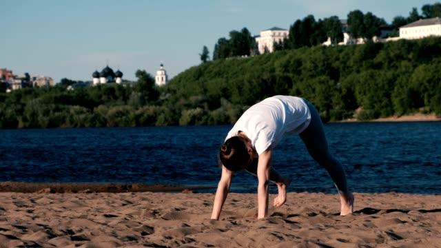 Mujer-haciendo-yoga-en-la-playa-por-el-río-en-la-ciudad-Vista-hermosa-de-Urdhva-Mukha-shvanasana-plantean-