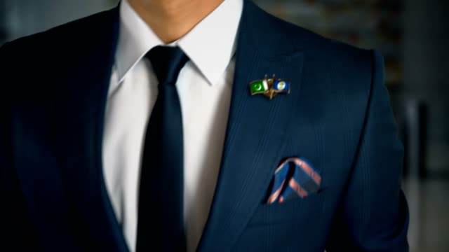 Businessman-Walking-Towards-Camera-With-Friend-Country-Flags-Pin-Pakistan---Belize
