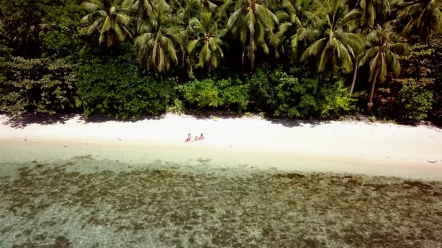 Drone-shot-aerial-view-of-Young-couple-relaxing-on-tropical-beach-in-the-Philippines-Islands-People-travel-luxury-vacations-destinations-concept