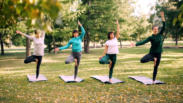 Concentrated-young-ladies-are-balancing-on-one-leg-with-raised-arm-in-Tree-pose-then-lowering-hands-in-Namaste-and-relaxing-Nature-recreation-and-sports-concept-