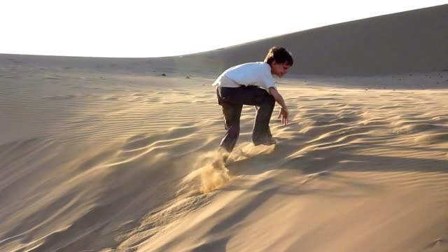 Junge-springen-und-Rollen-down-sanddune,-am-späten-Nachmittag