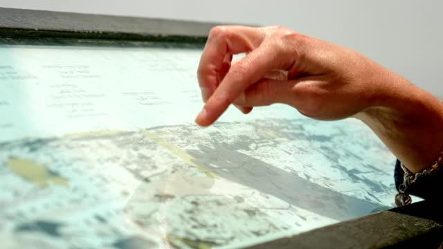 Händen-Zeigefinger-zeigt-die-Orte-auf-touristische-Karte
