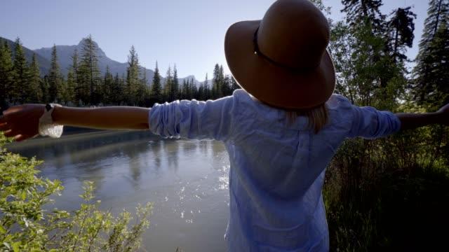 Junge-Frau-üben-Atemübung-durch-den-Fluss-umgeben-von-Natur