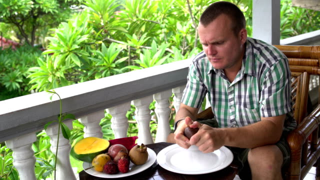 Man-sitting-on-the-balcony-cleans-the-Salacca-fruit-and-eats