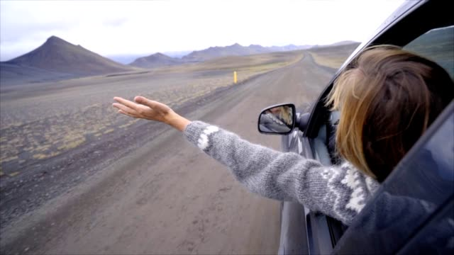 Cheerful-caucasian-female-inside-car-looking-at-road-arms-outstretched-mountain-volcanic-landscape-Road-trip-concept-Blond-hair-girl-looking-at-landscape-SLOW-MOTION