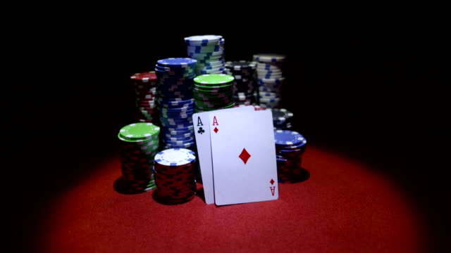 Teo-aces-and-stack-of-gambling-chips-on-red-casino-table