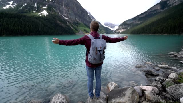Young-man-arms-outstretched-at-Lake-Louise