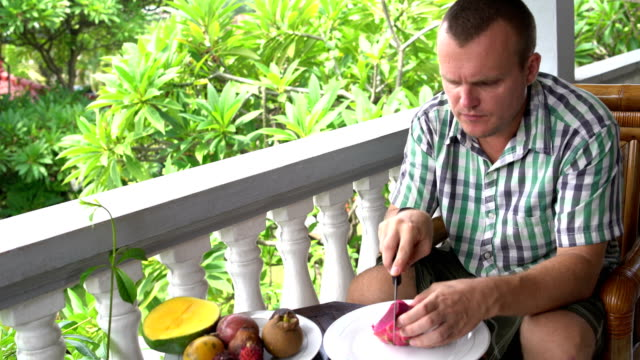 Man-sitting-on-the-balcony-cleans-the-Pitahaya-fruit-and-eats