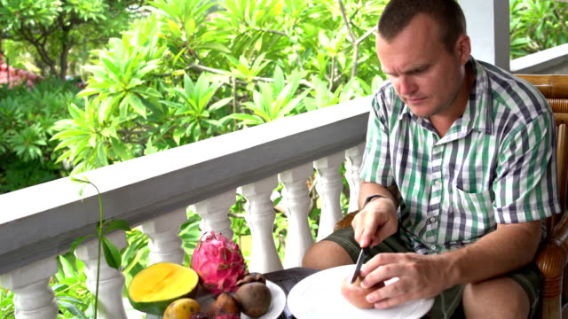 Man-sitting-on-the-balcony-cleans-the-passion-fruit-and-eats