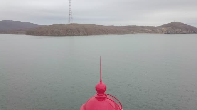 Ansicht-von-oben-rote-Dach-des-Leuchtturm-im-Meer-auf-Gebirgshintergrund