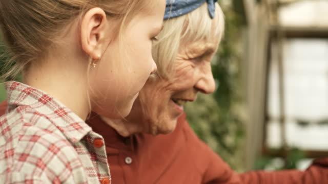 Senior-mujer-y-niña-en-jardín
