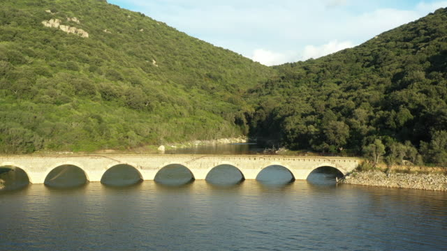 Video-from-above-aerial-view-of-a-Roman-bridge-on-a-beautiful-lake-sorrounded-by-some-green-hills-in-Sardinia-Italy-