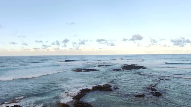 Flying-over-black-volcanic-stones-in-coastal-ocean-water