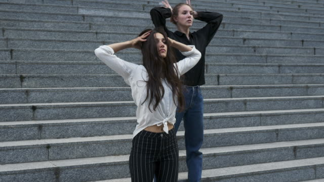 Two-Young-Woman-on-Exterior-Stairway-of-a-Building-in-Various-Dance-Poses